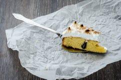 Una pieza de la torta bretona con los ciruelos y el merengue en una tabla de madera Foto de archivo
