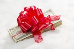 Una pila avvolta di cento banconote in dollari con il nastro rosso su neve Fotografia Stock