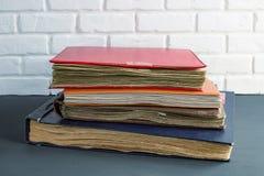 Una pila de álbumes de foto viejos contra una pared de ladrillo fotos de archivo libres de regalías