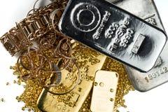 Una pila de barras del oro y de plata, de joyer?a del oro y de gr?nulos del oro fotos de archivo
