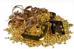 Una pila de barras de oro, de joyería del oro y de gránulos del oro Aislado en el fondo blanco fotos de archivo