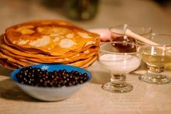 Una pila de blini caliente ruso fino de las crepes con las pasas, la miel, la crema agria y el atasco foto de archivo