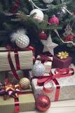 Una pila de cajas de regalo debajo de un árbol de navidad adornado Imagen de archivo libre de regalías