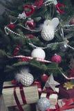 Una pila de cajas de regalo debajo de un árbol de navidad adornado Foto de archivo