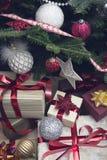 Una pila de cajas de regalo debajo de un árbol de navidad adornado Fotografía de archivo libre de regalías