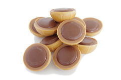 Una pila de chocolates del caramelo en el fondo blanco Imagen de archivo