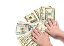 Una pila de cientos billetes de dólar en blanco aisló el fondo con las manos del ` s de los niños Foto de archivo
