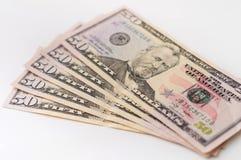 Una pila de cincuenta billetes de dólar avivó hacia fuera en un fondo blanco Fotografía de archivo