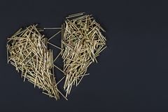 Una pila de clavos en la forma de un corazón quebrado foto de archivo libre de regalías