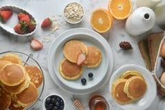 Una pila de crepe con los arándanos, fresas, anaranjadas en la tabla de mármol blanca Men? del desayuno imagen de archivo
