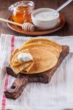 Una pila de crepes con la crema agria y la miel, Maslenitsa Fotografía de archivo