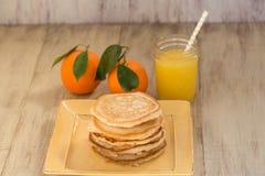 Una pila de crepes del desayuno con el zumo de naranja Foto de archivo