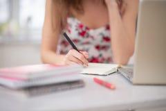 Una pila de cuadernos en el espiral y de estudiante en el ordenador portátil fotografía de archivo libre de regalías