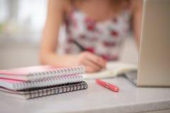 Una pila de cuadernos espirales y de estudiante en el ordenador portátil imagenes de archivo