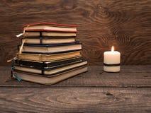 Una pila de cuadernos y una vela en una tabla de madera foto de archivo libre de regalías