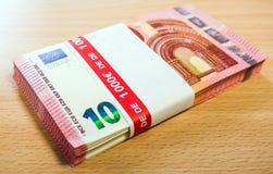 Una pila de diez cuentas euro en un escritorio del pino Fotografía de archivo libre de regalías