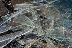 Una pila de diversos pedazos agudos de vidrio quebrado que mienten en la tierra fotos de archivo