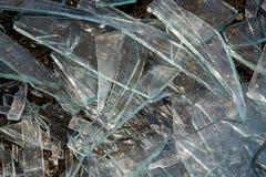 Una pila de diversos pedazos agudos de vidrio quebrado que mienten en la tierra imágenes de archivo libres de regalías