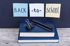 Una pila de dos libros en los cuales están los efectos de escritorio y los papeles con la inscripción de nuevo a escuela Fotografía de archivo