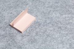Una pila de etiquetas engomadas de papel miente en un fondo gris claro del fieltro Fotos de archivo libres de regalías