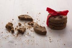 Una pila de galletas del chocolate de la Navidad ató una cinta roja Galletas quebradas, muchas migas en la tabla Imagenes de archivo