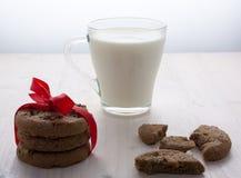 Una pila de galletas del chocolate de la Navidad ató una cinta roja Galletas quebradas, muchas migas en la tabla Un transparente Fotos de archivo libres de regalías