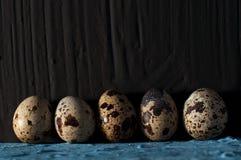 Una pila de huevos de codornices contra cierre negro del fondo para arriba Imagen de archivo