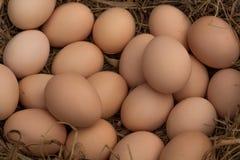 una pila de huevos marrones en una jerarquía en un fondo de la arena, porciones de huevos Fotos de archivo libres de regalías