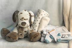 Una pila de la ropa de los niños, juguetes, pacificador en un backgr blanco Foto de archivo libre de regalías