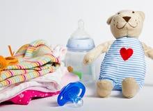 Una pila de la ropa de los niños, juguetes, pacificador Imagen de archivo libre de regalías