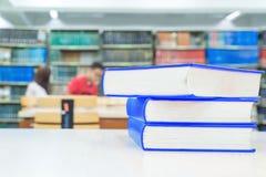 Una pila de libros con la biblioteca en la parte posterior Imagenes de archivo