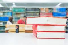 Una pila de libros con la biblioteca en la parte posterior Fotos de archivo