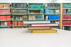 Una pila de libros con la biblioteca en la parte posterior Foto de archivo
