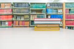 Una pila de libros con la biblioteca en la parte posterior Imágenes de archivo libres de regalías