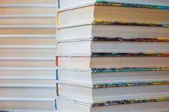 Una pila de libros en cubiertas multicoloras en la biblioteca o la librería imagen de archivo libre de regalías
