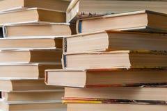 Una pila de libros en cubiertas multicoloras en la biblioteca o la librería imagenes de archivo
