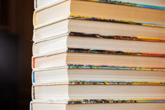 Una pila de libros en cubiertas multicoloras en la biblioteca o la librería fotos de archivo libres de regalías