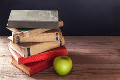 Una pila de libros viejos del vintage y de una manzana verde en una tabla de madera rústica Fotografía de archivo libre de regalías