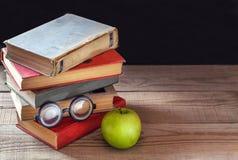 Una pila de libros viejos del vintage y de una manzana verde en una tabla de madera rústica Imagen de archivo libre de regalías