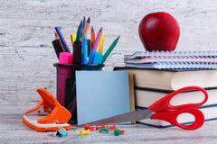 Una pila de libros y de cuadernos, efectos de escritorio, una manzana roja y vacia las hojas coloreadas con un lugar para escribi Fotos de archivo