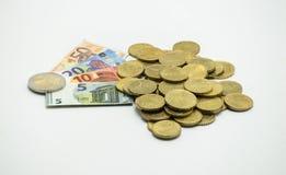 Una pila de monedas, el EURO europeo de la moneda con los billetes de banco miniatura 5, 10, 20, EURO 50 Aislado en el fondo blan Foto de archivo