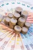 Una pila de monedas en billetes de banco Imagen de archivo libre de regalías