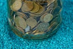 Una pila de monedas en un tarro de cristal en la arena azul imagenes de archivo