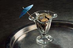 Una pila de monedas en un vidrio de cóctel Fotografía de archivo