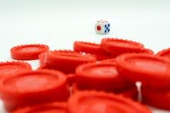 Una pila de monedas y de dados rojos imagenes de archivo