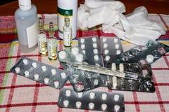 Una pila de píldoras, de drogas y de un termómetro en una servilleta fotografía de archivo