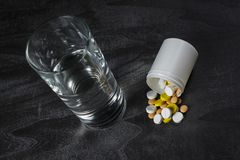 Una pila de píldoras en una tabla con un vidrio de agua Foto de archivo libre de regalías
