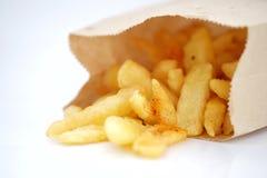 Una pila de patatas fritas aisladas en la envoltura de papel Fotografía de archivo libre de regalías