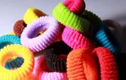 Una pila de pelo elástico colorido congriega con la iluminación lateral Imagenes de archivo