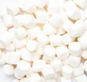 Una pila de pequeñas melcochas hinchadas blancas en el fondo blanco. Cl imagen de archivo